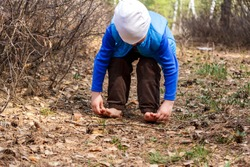 a four-year-old child walks barefoot on dry grass and leaves in the forest in the spring