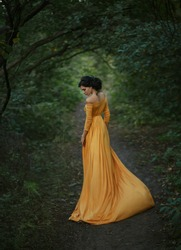 A fragile, tender girl in a yellow vintage dress . Background of a mystical arch of green trees. Artistic Photography