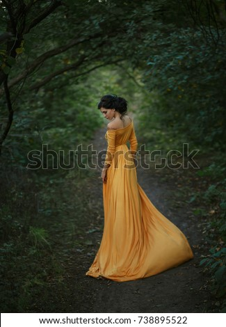 Stock Photo A fragile, tender girl in a yellow vintage dress . Background of a mystical arch of green trees. Artistic Photography