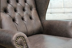 A fragment of a classic leather chair.Close-up of elegant leather texture with buttons. Fragment of a classic chair. With free space for text.