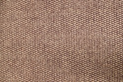 A fragment of a fluffy fleecy foot rug containing a pattern of beige and brown orderly alternating woolen details of a braided pattern with a tufted wool texture