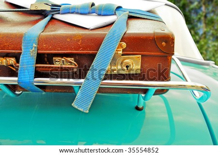 a fragment of a photo where a car has a porter, a brown suitcase is there, on the suitcase is a letter lying, bound to the porter with a blue cord