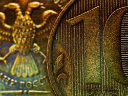A fragment of a Russian coin in 10 ten rubles close up. Dark impressive illustration. Economy, finance and banks of Russia. Scratched coins from circulation. Macro