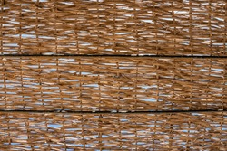 A fragment of a wicker wooden canopy from the sun made of branches, a beach umbrella for vacationers at a seaside resort.