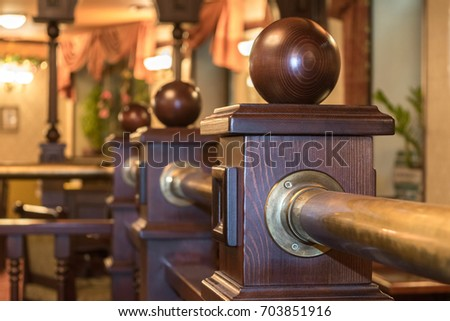 A fragment of a wooden fence in the interior of the restaurant or cafe. The fence posts with wooden balls. In the background is a cozy and comfortable interior with lamps and curtains. #703851916