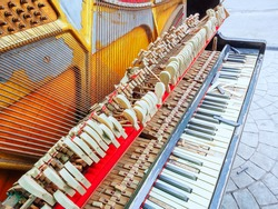 A fragment of an old broken piano with a missing wall and broken keys. Front view