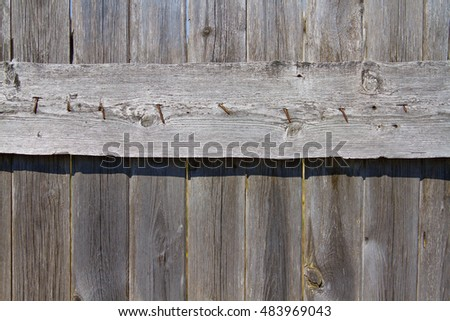 A fragment of an old wooden fence. Traditional rural construction #483969043
