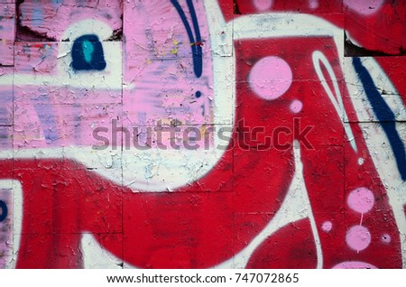 A fragment of graffiti drawing using contours, applied to the wall with the help of cans with aerosol paints over the colored filling areas. Background texture of street art and vandalism #747072865