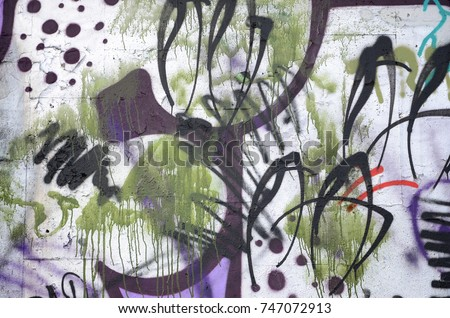 A fragment of graffiti drawing using contours, applied to the wall with the help of cans with aerosol paints over the colored filling areas. Background texture of street art and vandalism #747072913
