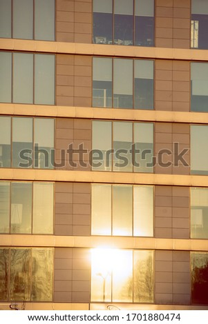 A fragment of the fa?ade plane with windows reflecting the shining morning sun. Photo stock ©