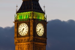 A fragment of the famous tower of Big Ben. The tower officially called the Elizabeth Tower. Close-up of the clock dials with night illumination of the building. Evening. London, UK.