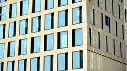 A fragment of the glass and sandstone facade of a modern office building. Wide abstract fragment of modern building facade. View of modern glass and stone facade.