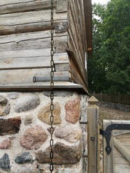 a fragment of the stone masonry foundation and wooden wall of an old historic building