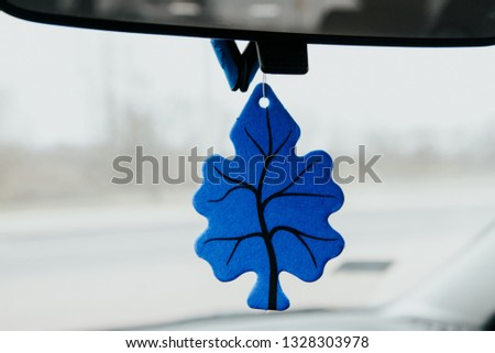 A fragrance pendant in the car. Blue pendant on the rearview mirror. The concept of maintaining a nice fragrance in the car. Caring for the car and order in the car.