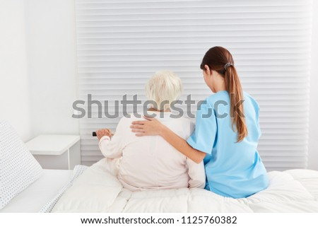 A frail old elderly woman as a patient gets help getting out of bed