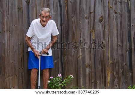 A frail one hundred year old centenarian senior citizen man with a cane standing by a wooden fence. Ample room for text in negative space over the fence.