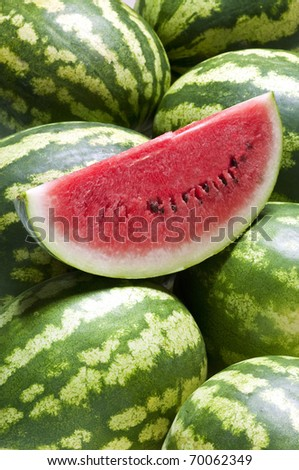 a frame full of watermelons and a slice on them