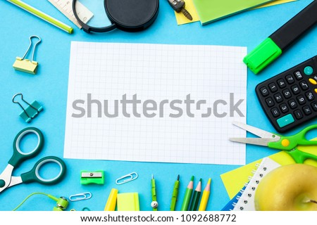 A frame of school subjects on a blue background. Ruler, scissors, calculator, pencils. View from above
