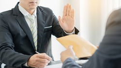 A fraudulent partner sells a contract and sends a paper pack containing cash to a colleague holding a pen to sign a corrupt contract, bribing but is denied.