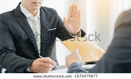 A fraudulent partner sells a contract and sends a paper pack containing cash to a colleague holding a pen to sign a corrupt contract, bribing but is denied. Stock photo ©