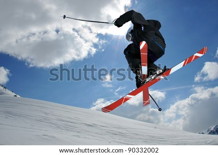 A free-ride ski jumper, with skis crossed against a blue sky with clouds