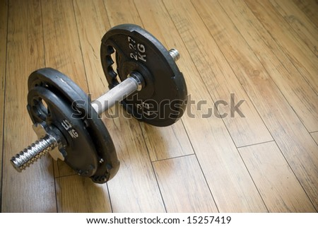 A free weight dumbell sitting on a wood floor - the perfect accessory to any home gym.