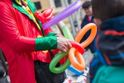A freelance clown creating balloon animals and different shapes at outdoor festival in city centre. School bag, angel wings, butterflies and dogs made of balloons. Concept of entertainment, birthdays