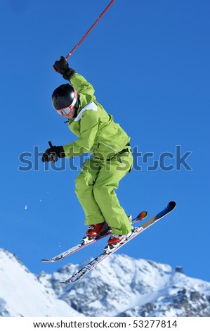 a freestyle ski jumper in green clothes performing a high jump