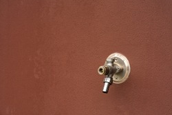 A freezeless stainless steel faucet mounted on the wall of the facade of the house.