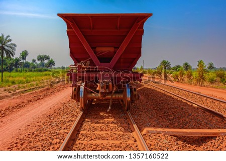 A freight train carrying bauxite in railway carriages for transhipment into a capesize bulk carrier ships by covered conveyor belt mechanism in the Kamsar, Guinea, Africa.
