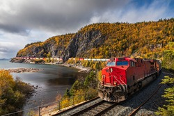 A freight train hauls shipping containers through the rugged landscape.