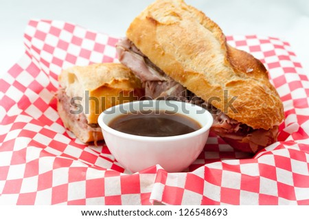 a french dip or beef dip on a baguette with dipping sauce or au jus