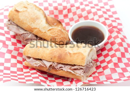 a french dip or beef dip on a baguette with dipping sauce or au jus - stock photo