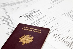 A French passport on the top of an Canadian application form to obtain a Permanent residence visa.