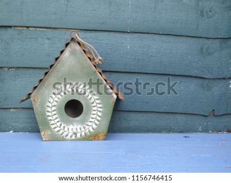 A French shabby chic style decorative green metal birdhouse on a blue wooden bench with wood panel background , a colourful garden decoration  #1156746415