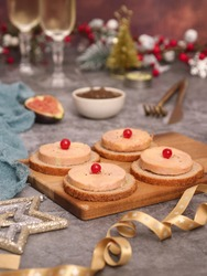 A French traditional foie gras topped on toaster bread on a wooden plate aside with onion marmalade and a piece of fig fruit,  glasses of Champagne in background, with Christmas atmosphere decoration.