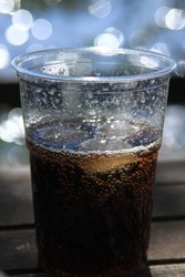 A fresh and cold cola drink with three ice cubes in plastic mug on a blurry, dark brown wooden table, sparkling all the way in the mug,