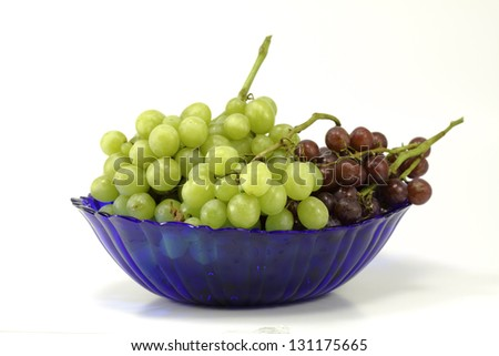 A fresh cluster of green and purple grapes isolated against a white background with room for copy