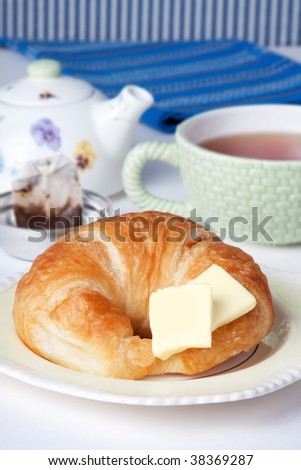 A fresh croissant with two pats of butter. Tea cup, tea pot and tea bag in background.