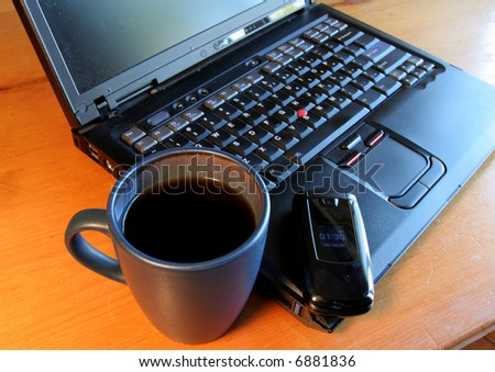 A fresh cup of sitting on in front of a laptop and a mobile phone.