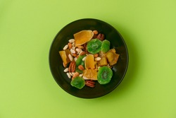A fresh dried and candied fruits and nuts in black bowl on green bakground. Concept of nutrient and healty breakfast or meal and vegan or vegetarian food.