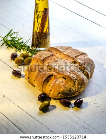 A fresh from the oven olive loaf standing on a white board lit with a golden shaft of morning light with olives and rosemary and a bottle of spiced olive oil.  #1535123714