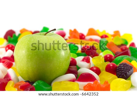 A fresh green apple on a background of assorted candy.