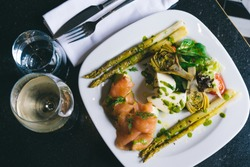 A fresh healty plate with artichoke, smoked salmon, mozzarella and asparagus and white wine on the side