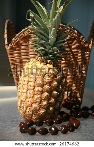 a fresh picked pineapple with a Kukui Nut Lei against a wicker basket