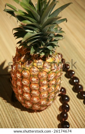 "a fresh pineapple with a ""KUKUI NUT LEI"" on a bamboo mat"
