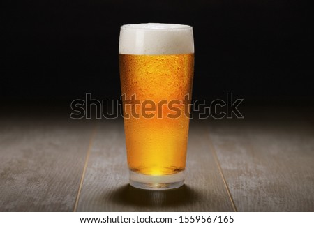 A fresh pint of India Pale ale IPA craft beer served in a cold pint glass at a brewery, black background Stockfoto ©