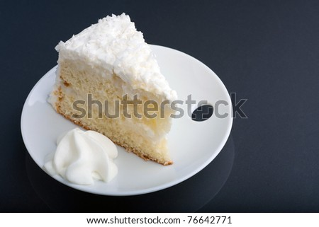 A fresh slice of coconut cream cake on a white plate.