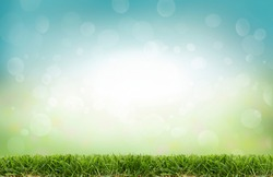 A fresh spring, summer sunny blue sky background with green grass lawn and blurred bokeh glow.