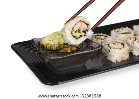 A fresh sushi roll of crab and fish being dipped into wasabi and soy sauce using chopsticks and an elegant serving tray.